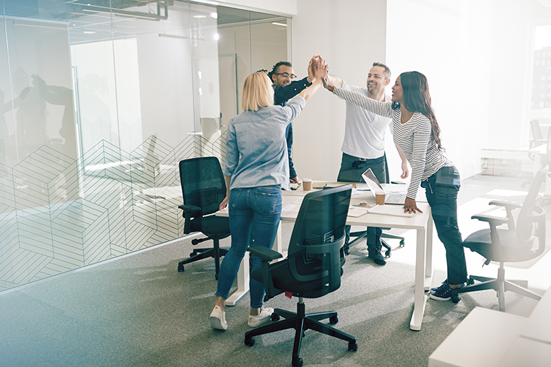 Smiling colleagues standing together around an office table high fiving